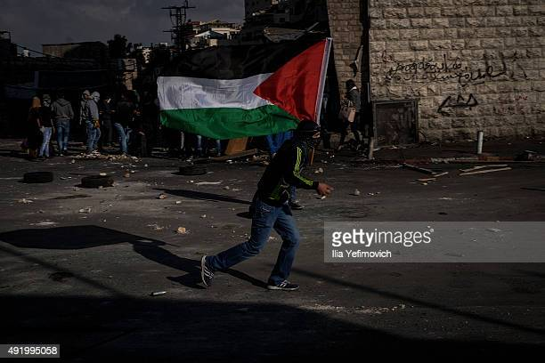 Palestinian protester holds a flag as he clashes with Israeli border police on October 9 2015 in Shuafat refugee camp in Jerusalem Israel As tension...