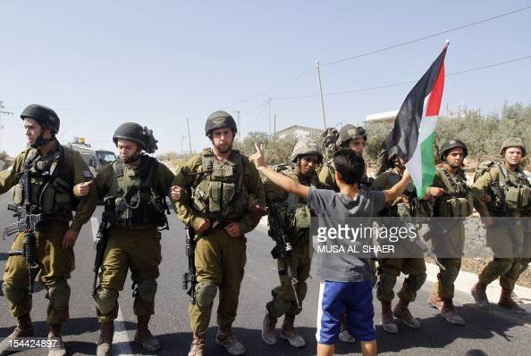 A palestinian protester holds a national flag as he stands in front of Israeli soldiers during a protest against Israel's controversial separation...