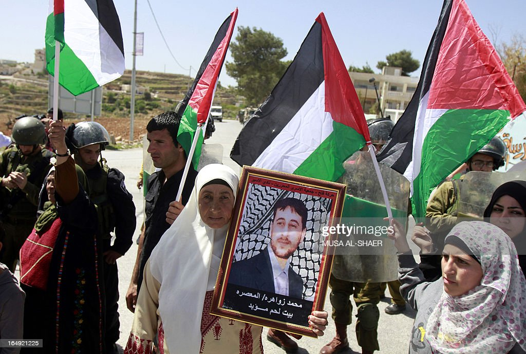 A Palestinian protester holds a picture of a relative detained in an Israeli jail as others wave Palestinian flags during a weekly demonstration against the Israeli separation barrier and the expansion of Jewish settlements, in the West Bank village of Maasarah, near Bethlehem, on March 29, 2013. Israel deployed significant security reinforcements in the occupied West Bank including east Jerusalem for demonstrations commemorating the deaths in 1976 of Arab Israelis on 'Land Day'. AFP PHOTO/MUSA AL-SHAER