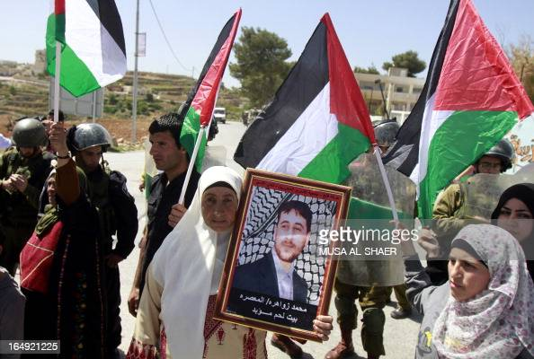 A Palestinian protester holds a picture of a relative detained in an Israeli jail as others wave Palestinian flags during a weekly demonstration...