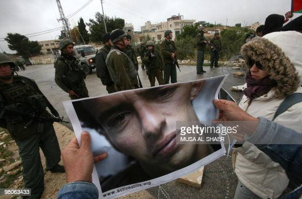 A Palestinian protester holds a picture of Omar Zawahreh an activist who was arrested by the Israeli army a few days ago opposite Israeli soldiers...