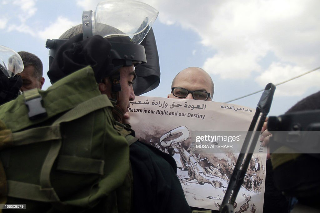 A Palestinian protester holds a poster during a demonstration against the construction of a gate which isolates one of the houses in the village behind the controversial Israeli separation barrier, in the West Bank village of Walajeh, near the biblical West Bank town of Bethlehem, on May 10, 2013. AFP PHOTO/MUSA AL SHAER