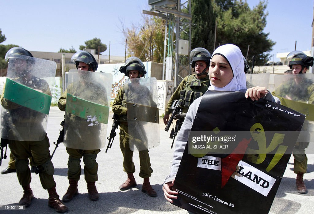 A Palestinian protester holds a poster for Land Day, which commemorates the deaths in 1976 of Arab Israelis during mass demonstrations against plans to confiscate Arab land in Galilee, as she stands in front of Israeli soldiers during a weekly demonstration against the Israeli separation barrier and the expansion of Jewish settlements, in the West Bank village of Maasarah, near Bethlehem, on March 29, 2013. Israel deployed significant security reinforcements in the occupied West Bank including east Jerusalem for demonstrations marking Land Day. AFP PHOTO/MUSA AL-SHAER