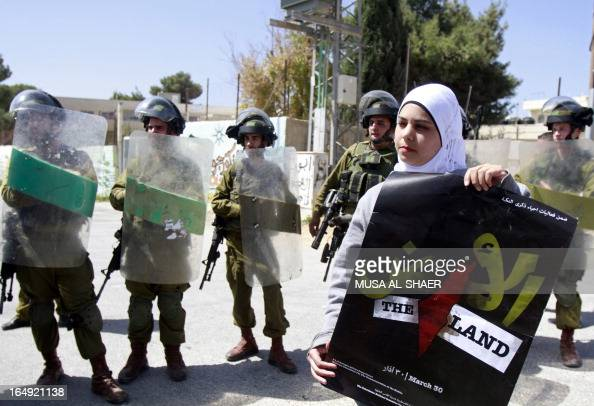 A Palestinian protester holds a poster for Land Day which commemorates the deaths in 1976 of Arab Israelis during mass demonstrations against plans...