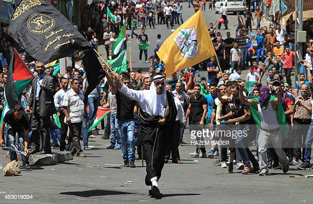 A Palestinian protester holds an islamic flag walking towards Israeli forces during clashes in the West Bank town of Hebron on August 1 2014...