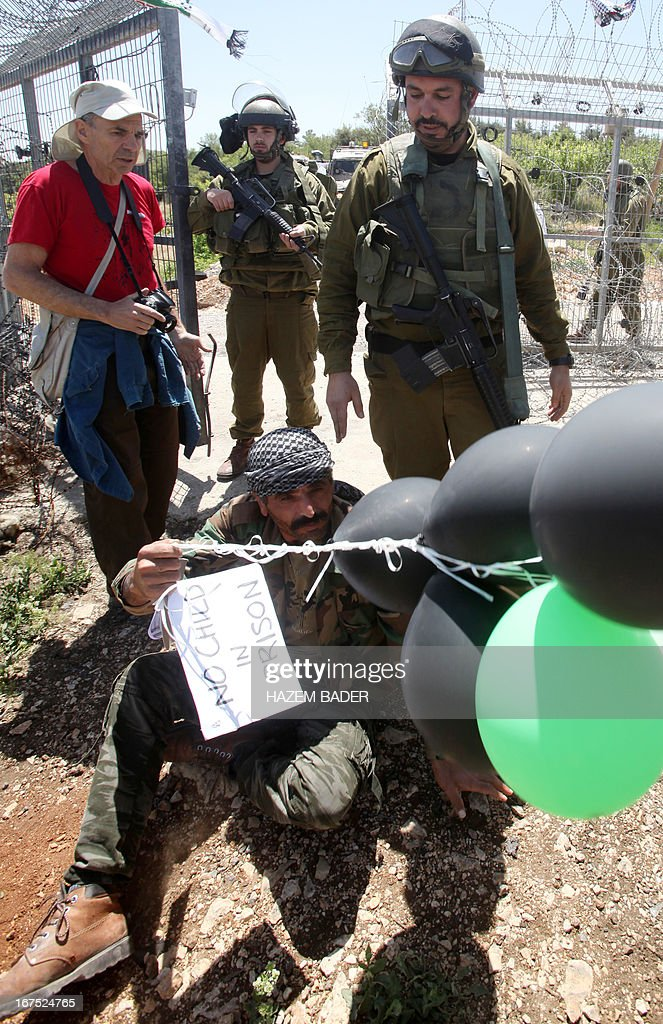 A Palestinian protester holds balloons and a placard in front of Israeli soldiers during a protest against settlement expansion on Palestinian land in the Beit Omar village, north the West Bank city of Hebron, on April 26, 2013. Israeli security forces overnight demolished two structures that Jewish settlers had erected to create a 'wildcat' outpost in the occupied West Bank, a police spokesman said on April 26.