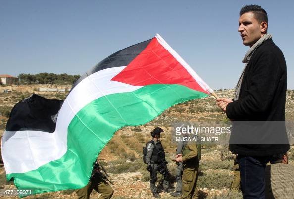 A Palestinian protester holds his national flag in front of Israeli security forces during a weekly protest against Israel's controversial separation...