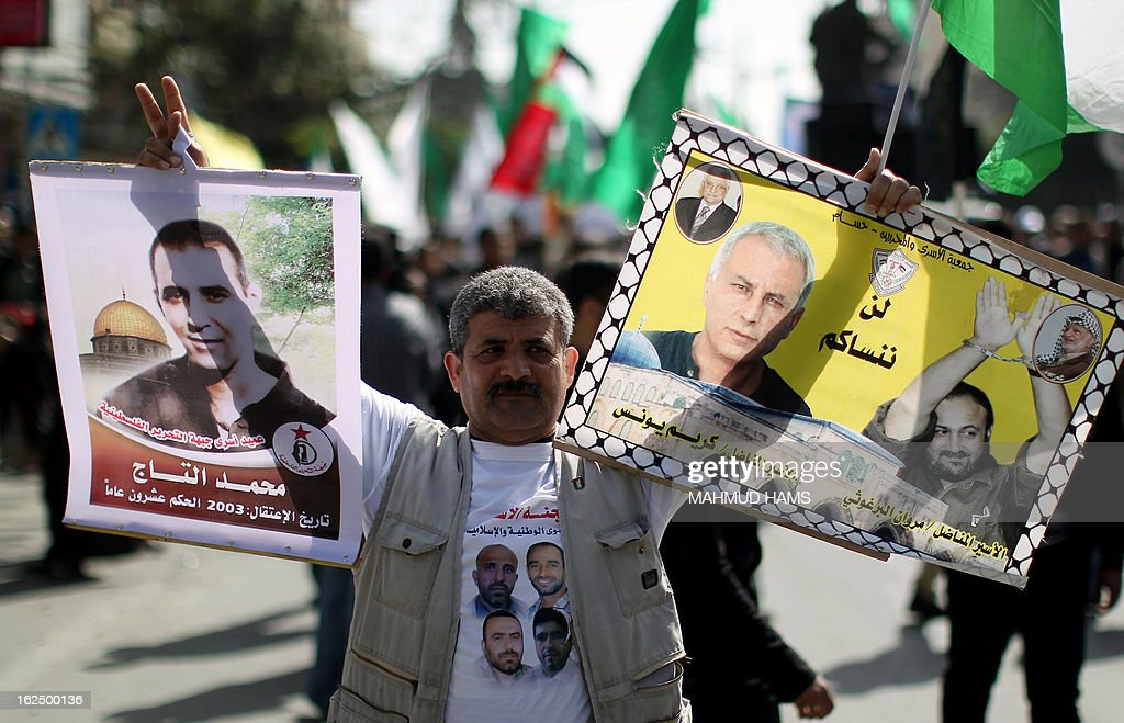 A Palestinian protester holds pictures of Israeli-held prisoners, including Fatah leader Marwan Barghuti (R), during a demonstration in Gaza City in solidarity with Palestinian prisoners on February 24, 2013. Some 3,000 Palestinians held in Israeli jails were staging a one-day hunger strike in protest at the death of an inmate, an official said, as security forces clashed with demonstrators in the West Bank.