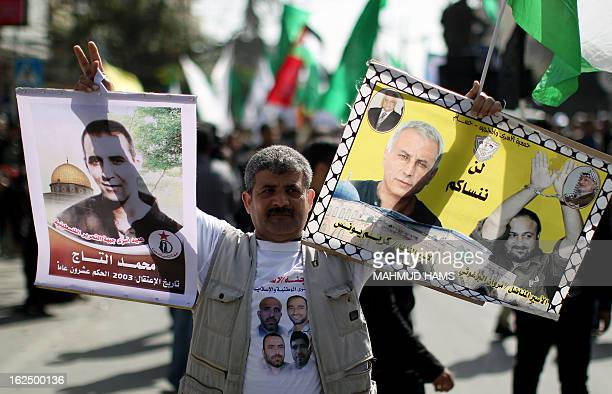 A Palestinian protester holds pictures of Israeliheld prisoners including Fatah leader Marwan Barghuti during a demonstration in Gaza City in...