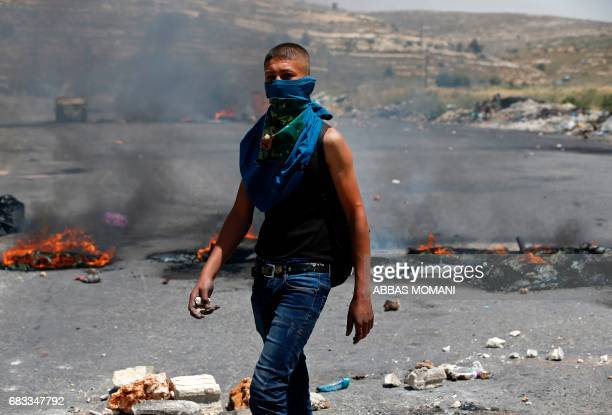 A Palestinian protester holds stones during clashes with Israeli security forces following a protest marking the 69th anniversary of Nakba which...