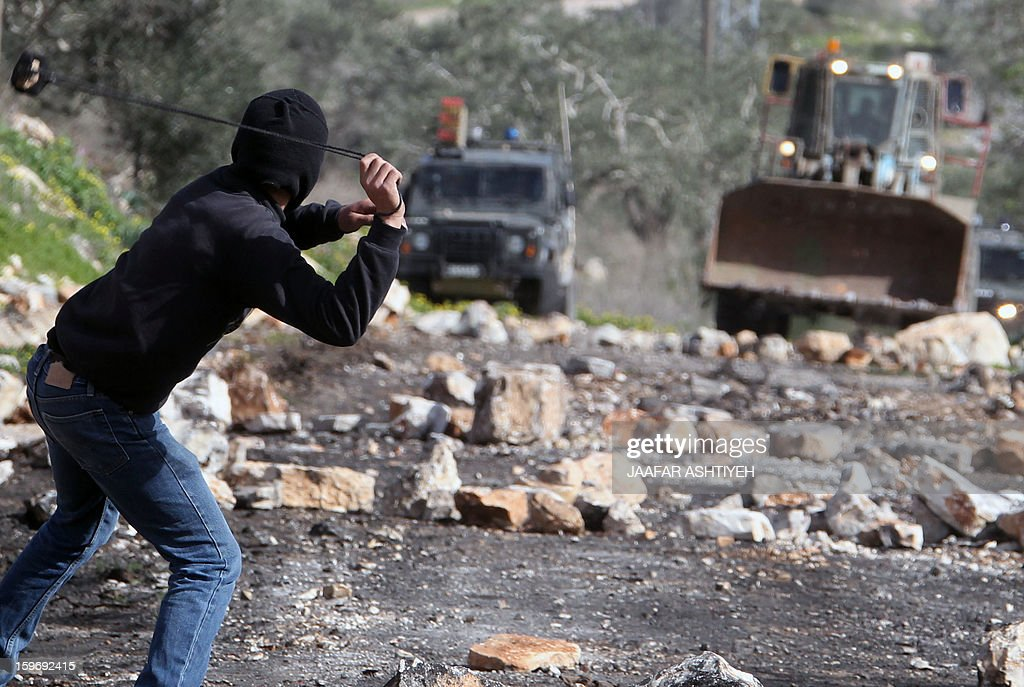 A Palestinian protester hulrs a stone towards Israeli forces during clashes following a protest against the expropriation of Palestinian land by Israel on January 18, 2013 in the village of Kafr Qaddum, near Nablus, in the occupied West Bank. AFP PHOTO/JAAFAR ASHTIYEH