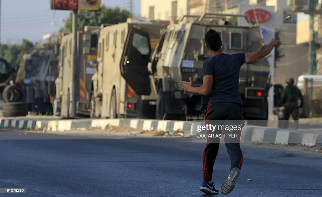 A Palestinian protester hurls a rock at Israeli soldiers on a street east of the West Bank city of Nablus on October 3 as they search for the...