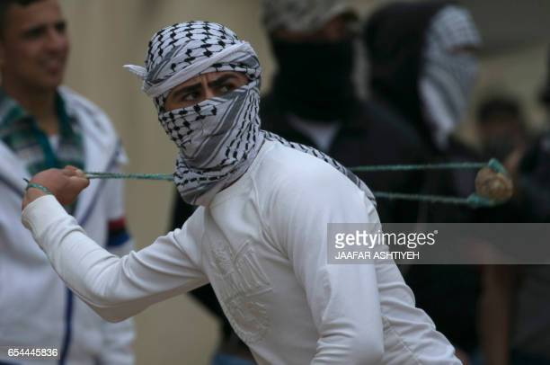 A Palestinian protester hurls a stone towards Israeli security forces during clashes following a weekly demonstration against the expropriation of...