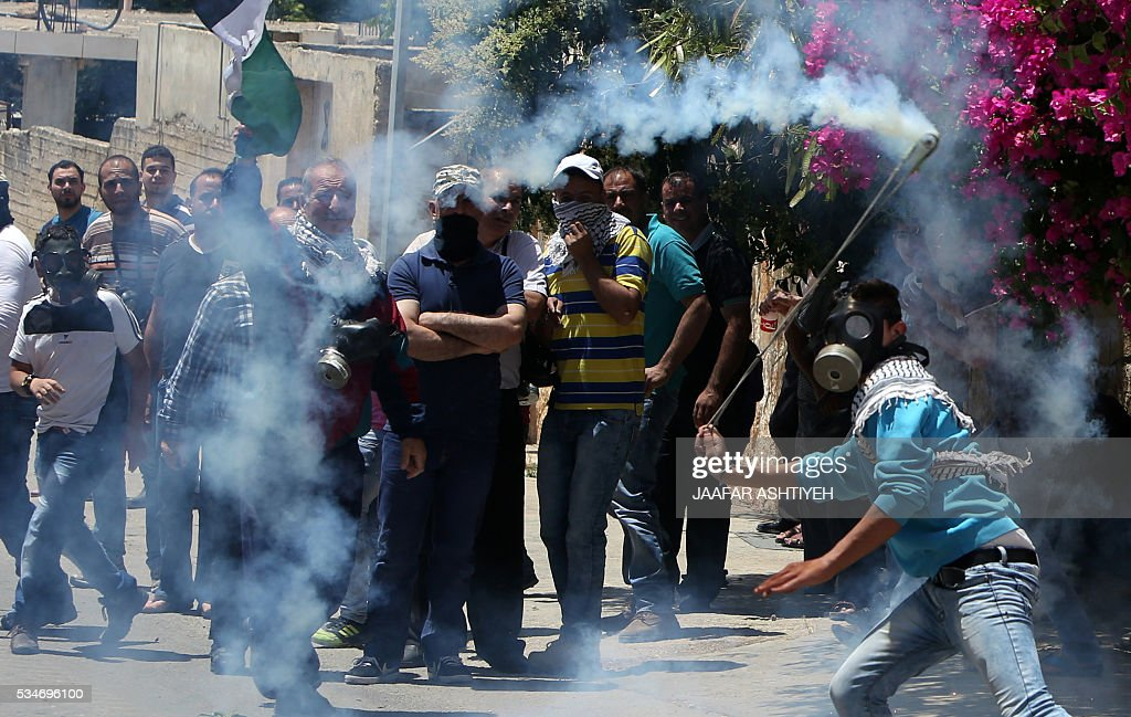 A Palestinian protester hurls a tear gas canister back towards Israeli security forces during clashes following a demonstration against the expropriation of Palestinian land by Israel, on May 27, 2016 in the village of Kfar Qaddum, near Nablus, in the occupied West Bank. / AFP / JAAFAR