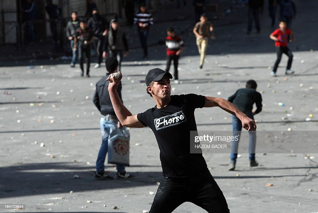 A Palestinian protester hurls rocks at Israeli police during clashes following increased security checks during the visit of Israeli Jews to the tomb of Othniel Ben Kenaz, considered holy by the Jewish faith, in the Palestinian side of the city of Hebron, on March 27, 2013. Religious Jews worldwide eat matzoth during the eight-day Pesach holiday that commemorates the Israelis' exodus from Egypt some 3,500 years ago and their ancestors' plight by refraining from eating leavened food products. AFP PHOTO/HAZEM BADER
