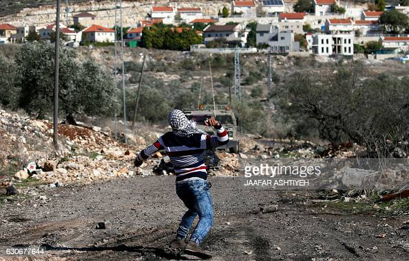 A Palestinian protester hurls rocks during clashes with Israeli security forces following a demonstration against the expropriation of Palestinian...