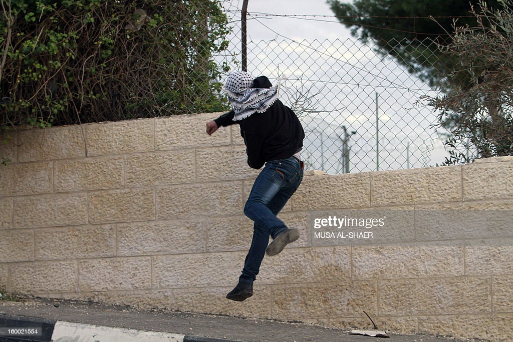 A Palestinian protester hurls stones at Israeli security forces during clashes in the Aida Palestinian refugee camp near the West Bank city of Bethlehem on January 24, 2013. The Palestinian leadership wants new dialogue with Israeli political parties, particularly centrists who emerged strong in this week's election, an official said. AFP PHOTO/MUSA AL-SHAER