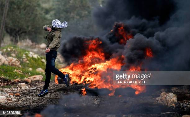 Palestinian protester hurls stones at Israeli security forces near a fire during clashes following a weekly demonstration against the expropriation...