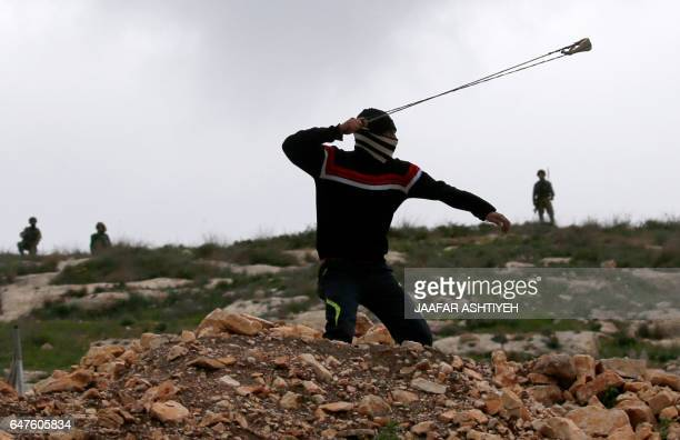 Palestinian protester hurls stones at Israeli security forces using a slingshot during clashes following a weekly demonstration against the...