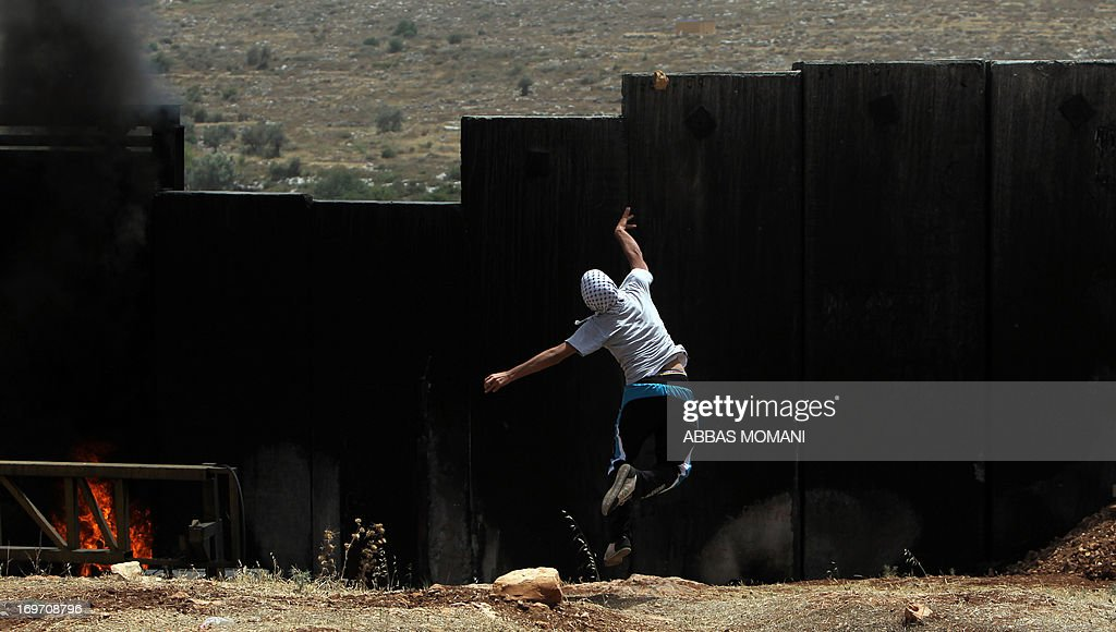 A Palestinian protester hurls stones over Israel's controversial separation barrier during clashes with Israeli security forces following a demonstration against Israeli settlements and its separation wall, in the West Bank village of Nilin on May 31, 2013.