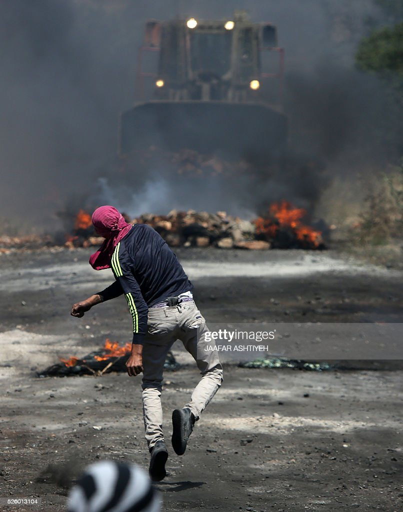 A Palestinian protester hurls stones towards a digger operated by Israeli security forces during clashes following a demonstration against the expropriation of Palestinian land by Israel on April 29, 2016 in the village of Kfar Qaddum, near Nablus, in the occupied West Bank. / AFP / JAAFAR