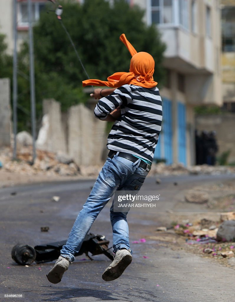 A Palestinian protester hurls stones towards Israeli security forces during clashes following a demonstration against the expropriation of Palestinian land by Israel, on May 27, 2016 in the village of Kfar Qaddum, near Nablus, in the occupied West Bank. / AFP / JAAFAR