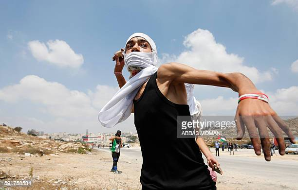 Palestinian protester hurls stones towards Israeli security forces during clashes following a demonstration in solidarity with Palestinian prisoners...