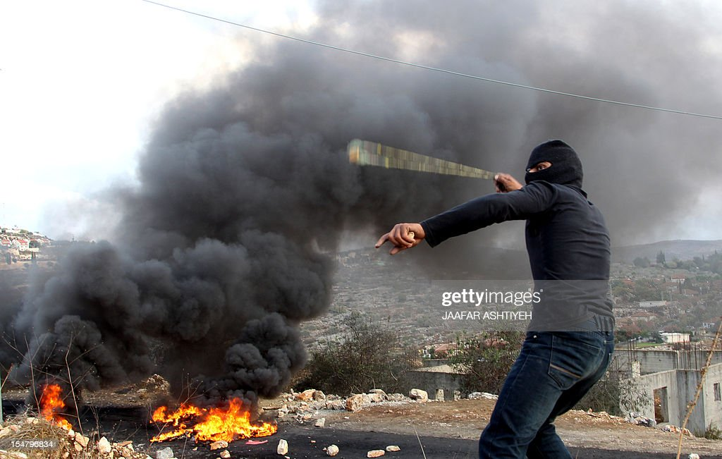 A Palestinian protester hurls stones towards Israeli soldiers during a demonstration against the expropriation of Palestinian land by Israel in the village of Kfar Qaddum, near the West Bank city of Nablus, on October 26, 2012.