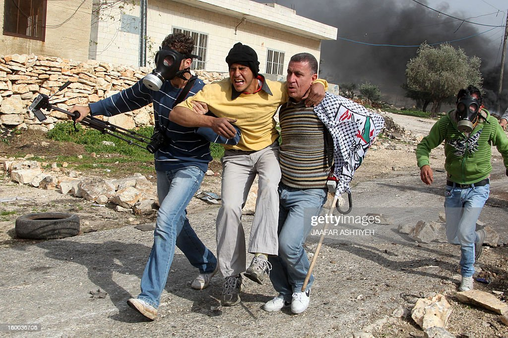 A Palestinian protester, is carried away after he inhaled tear gas during a protest against the expropriation of Palestinian land by Israel on January 25, 2013 in the village of Kafr Qadum, near Nablus, in the occupied West Bank.