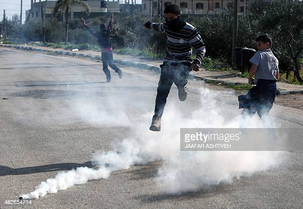 A Palestinian protester jumps amid the smoke of a tear gas canister during clashes with Israeli security forces following the demolition of a well...