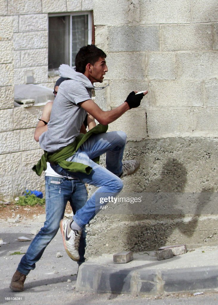A Palestinian protester jumps to throw stones towards Israeli soldiers during clashes following a rally marking Land Day in the al-khader village near the West Bank town of Bethlehem on March 30, 2013. The annual demonstrations mark the deaths of six Arab Israeli protesters at the hands of Israeli police and troops during mass protests in 1976 against plans to confiscate Arab land in the northern Galilee region.