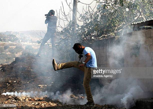 Palestinian protester kicks back a tear gas canister fired by Israeli security forces during clashes following a protest against the expropriation of...