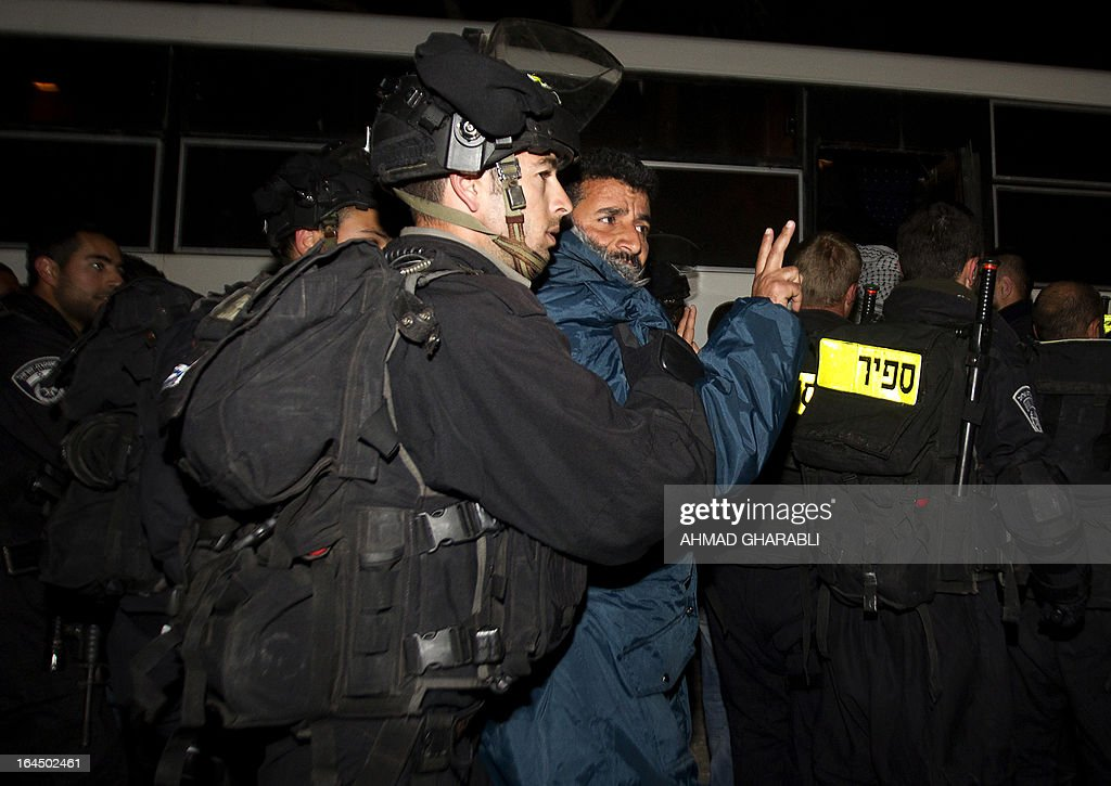 A Palestinian protester makes the victory sign as he is evacuated by Israeli border policemen from a protest camp in the controversial West Bank area known as E1 located east of Jerusalem and near the Jewish settlement of Maaleh Adumim early on March 24, 2013. Hundreds of Israeli police dismantled the protest camp on the outskirts of Jerusalem overnight, activists and police said. Activists set up the camp, which they dubbed Bab al-Shams or 'Gate of the Sun' in Arabic, in a bid to draw attention to Israeli plans to boost settlement building in the area known as E1.