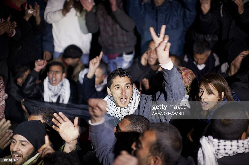 A Palestinian protester makes the victory sign as he shouts slogans with fellow demonstrators at a protest camp in the controversial West Bank area known as E1 located east of Jerusalem and near the Jewish settlement of Maaleh Adumim early on March 24, 2013. Hundreds of Israeli police dismantled the protest camp on the outskirts of Jerusalem overnight, activists and police said. Activists set up the camp, which they dubbed Bab al-Shams or 'Gate of the Sun' in Arabic, in a bid to draw attention to Israeli plans to boost settlement building in the area known as E1.
