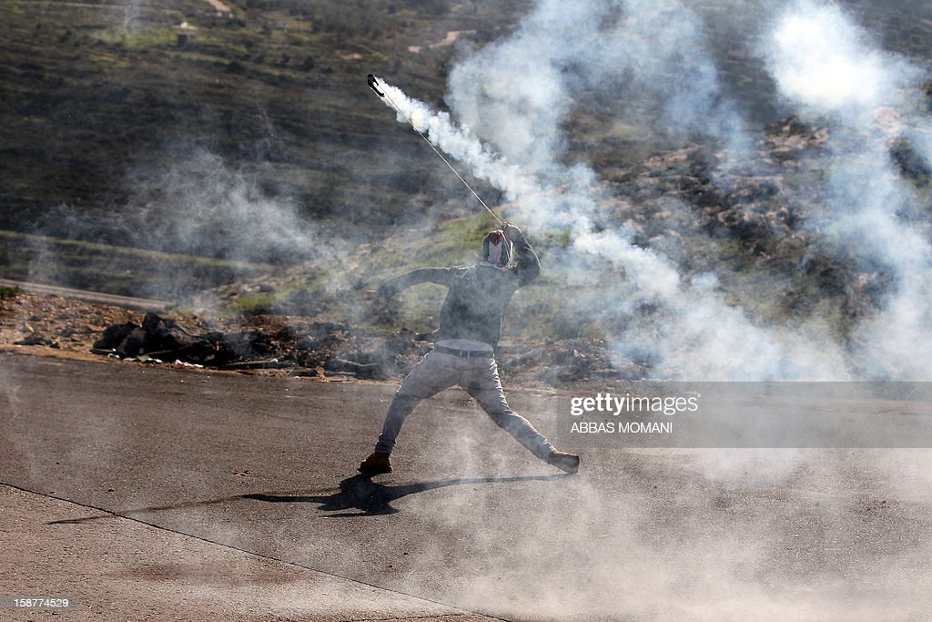 A Palestinian protester prepares to hurl back a tear gas canister fired by Israeli security forces during clashes that erupted following a march organised by residents of the West Bank village Nabi Saleh to protest against the expansion of Jewish settlements on Palestinian land on December 28, 2012. AFP PHOTO/ABBAS MOMANI