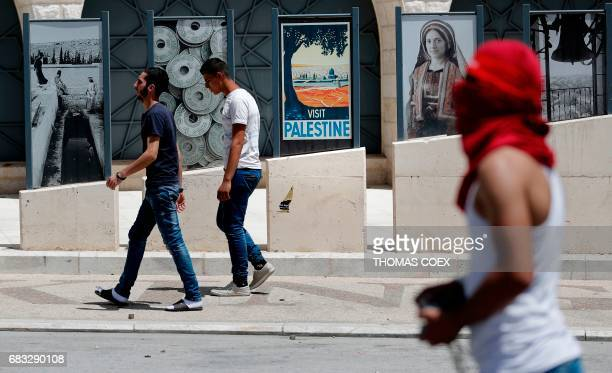 Palestinian protester prepares to throw stones during clashes with Israeli security forces following a demonstration to mark the 69th anniversary of...