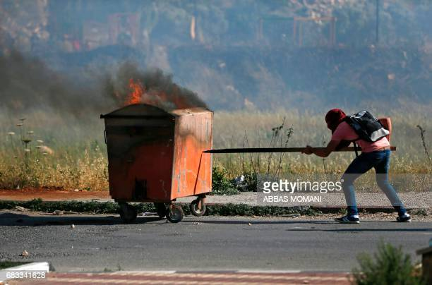 A Palestinian protester pushes a bin on fire during clashes with Israeli security forces following a protest marking the 69th anniversary of the...