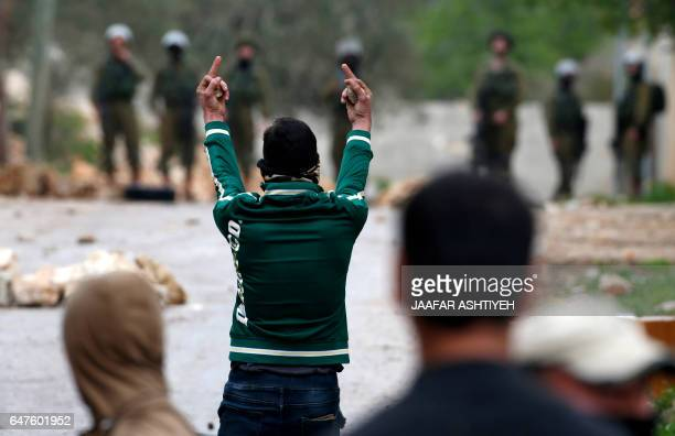 Palestinian protester raises his middle fingers at Israeli security forces during clashes following a weekly demonstration against the expropriation...