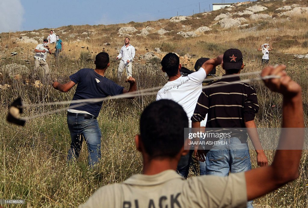 A Palestinian protester readies to throw a stone with his slingshot towards Israeli settlers from the Yitzhar Jewish settelment during clashes on May 19, 2012 near the city of Nablus in the Israeli occupied Palestinian West Bank. According to Palestinian eyewitnesses and security forces, fifty settlers attacked Palestinians there with stones. The Israeli army fired tear gas to disperse the clashes, and two Palestinians were wounded by stones, the Palestinian sources said.