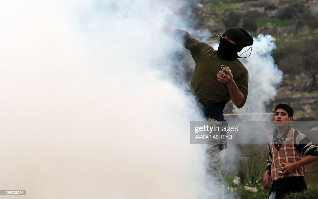 A Palestinian protester rethrows smoke devices during a protest against the expropriation of Palestinian land by Israel on January 11, 2013 in the village of Kafr Qaddum, near Nablus, in the occupied West Bank.