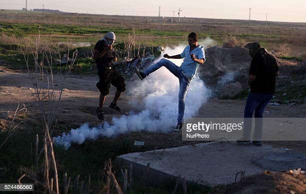 A Palestinian protester returns a teargas canister fired by Israeli troops during clashes near the border between Israel and Central Gaza Strip...