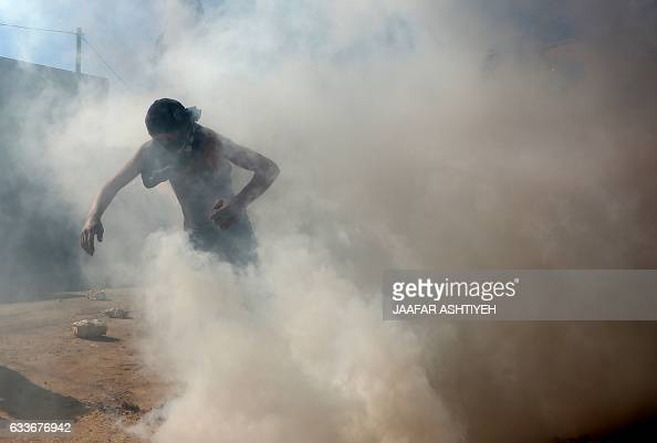 A Palestinian protester run from a teargas cloud during clashes with Israeli security forces following a weekly demonstration against the...