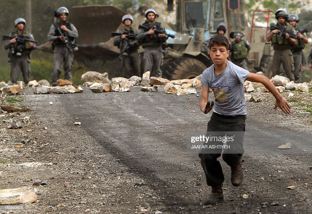 A Palestinian protester runs away from Israeli border guards during clashes following a protest against the expropriation of Palestinian land by Israel on March 8, 2013, in the village of Kafr Qaddum, near the occupied West Bank city of Nablus. AFP PHOTO/JAAFAR ASHTIYEH