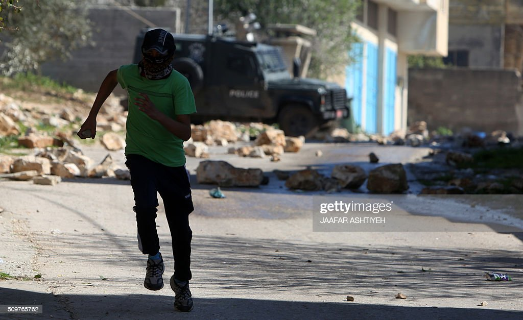 A Palestinian protester runs for cover during clashes with Israeli soldiers following a demonstration against the expropriation of Palestinian land by Israel on February 12, 2016 in the village of Kfar Qaddum, near Nablus in the occupied West Bank. / AFP / JAAFAR ASHTIYEH
