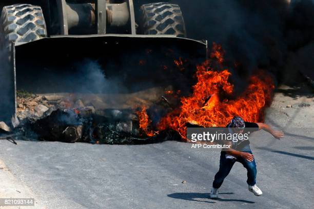 A Palestinian protester runs from the path of an Israeli army bulldozer during clashes in the village of Kobar west of Ramallah on July 22 as Israeli...