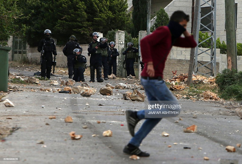 A Palestinian protester runs in front of a line of Israeli security forces during clashes following a weekly demonstration against the expropriation of Palestinian land by Israel in the village of Kfar Qaddum, near Nablus, in the occupied West Bank, on May 6, 2016. / AFP / JAAFAR