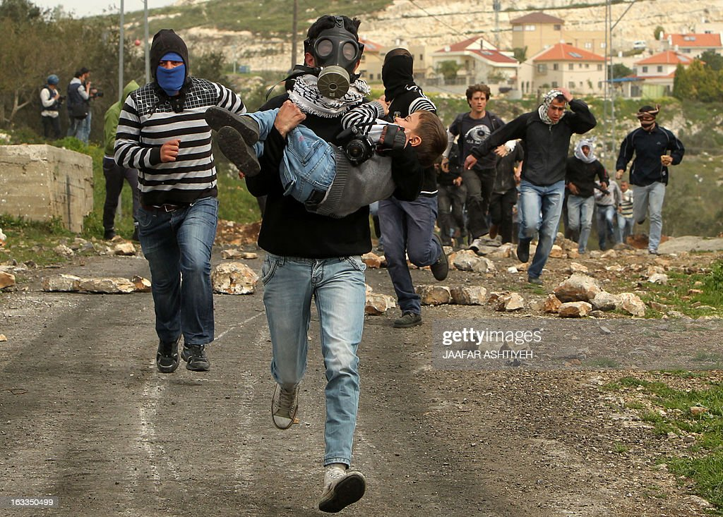 A Palestinian protester runs with a young boy in his arms during clashes with israeli security forces following a protest against the expropriation of Palestinian land by Israel on March 8, 2013, in the village of Kafr Qaddum, near the occupied West Bank city of Nablus.