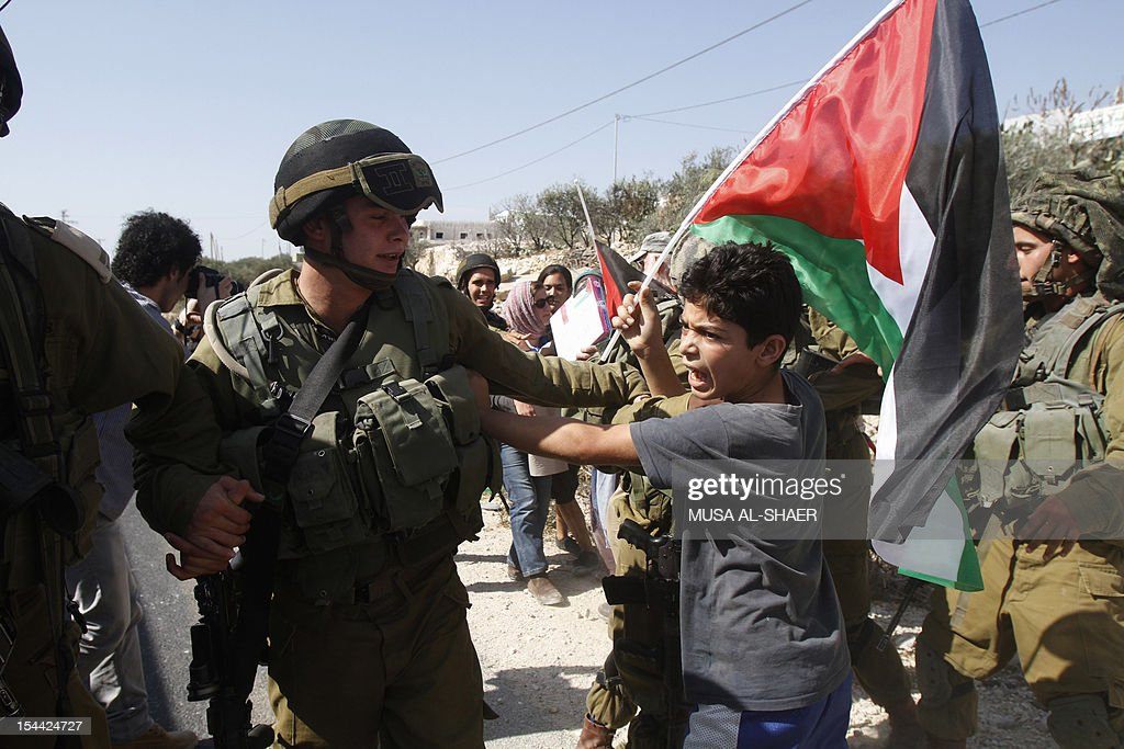 A palestinian protester scuffles with an Israeli soldier during a protest against Israel's controversial separation barrier in the West Bank village of Maasarah near Bethlehem on October 19, 2012 as they mark the sixth anniversary of the start of weekly demonstrations against the wall.
