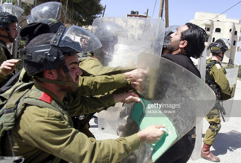 A Palestinian protester scuffles with Israeli soldiers following a weekly demonstration against the Israeli separation barrier and the expansion of Jewish settlements, in the West Bank village of Maasarah, near Bethlehem, on March 29, 2013. Israel deployed significant security reinforcements in the occupied West Bank including east Jerusalem for demonstrations commemorating the deaths in 1976 of Arab Israelis on 'Land Day'.