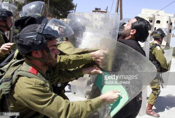 A Palestinian protester scuffles with Israeli soldiers following a weekly demonstration against the Israeli separation barrier and the expansion of...